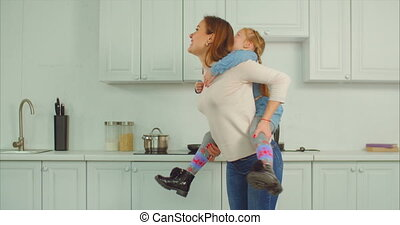 Carefree mother piggybacking excited kid in kitchen -...