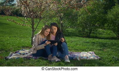 Carefree multiethnic women with tablet pc on park lawn