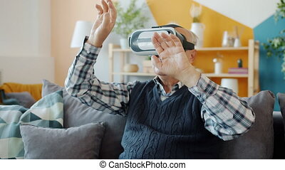 Carefree pensioner is using vr glasses at home moving arms sitting on couch in apartment enjoying contemporary device. People, gadgets and lifestyle concept.