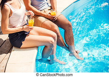 Carefree relax at the pool. Top view of couple in casual wear sitting poolside together and drinking cocktails