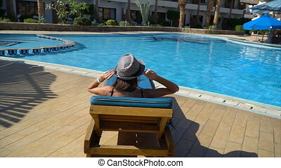 Carefree slim woman unwinds and sunbathes near swimming pool in a summer day