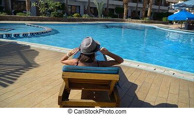Carefree slim woman unwinds and sunbathes near swimming pool...