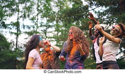 Carefree students are dancing at party tossing hair having great time, their faces, hair and clothing are dirty with paint. Holi celebration, youth and nature concept.