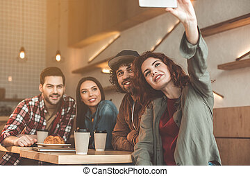 Carefree students photographing themselves on phone in cafeteria