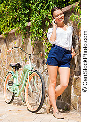 Carefree talk with friend. Beautiful young woman talking on the mobile phone and smiling while standing near her vintage bicycle