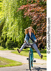 Carefree teenager riding bicycle across the park enjoying ...