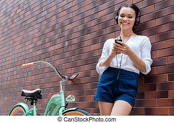 Carefree time. Beautiful young woman in headphones listening to MP3 player and smiling while standing near her vintage bicycle