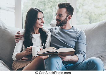 Carefree time together. Beautiful young loving couple looking at each other with smiles while sitting together on the couch