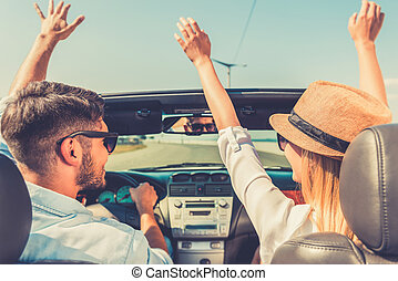 Carefree time together. Rear view of joyful young couple keeping arms raised while riding in their white convertible