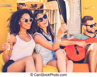 Carefree time with friends. Two cheerful young women holding bottles with beer and smiling while man playing the guitar with minivan in the background