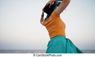 Carefree unusual woman with blue dyed hair dancing, spinning around on sea background. Femininity, vacation, vitality, healthy living concept. Hipster girl in hat having fun, laugh. FullHD footage.