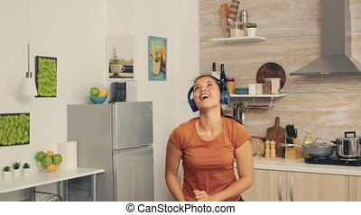 Carefree woman dancing in kitchen listening music on headphones. Energetic, positive, happy, funny and cute housewife dancing alone in the house. Entertainment and leiuse alone at home