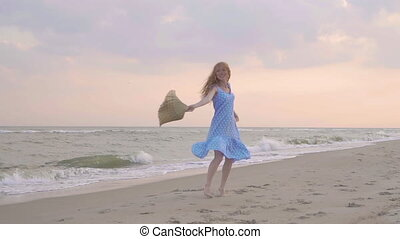 Carefree woman dancing on the sunset on the sea beach. Girl rotate with a straw hat in his hand . Femininity at sunset. Slow motion