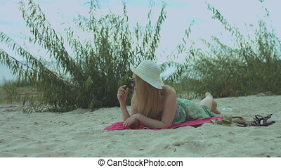 Carefree pretty redhead woman in stylish summer dress and hat relaxing at the beach while lying down on a towel. Attractive ginger female in sunglasses enjoying summer holidays vacation at seaside.