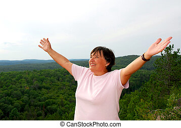 Mature woman on hilltop raising her arms