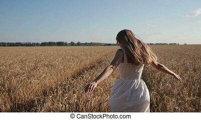 Carefree woman running through golden wheat field