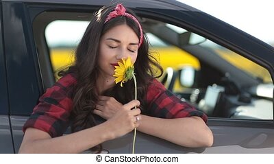 Carefree woman smelling sunflower on roadtrip - Charming...