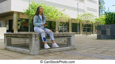 Carefree woman with skateboard listening to music on mobile ...