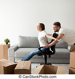 Carefree young couple having fun playing with office chair