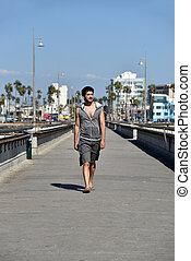 Carefree young tourist walking on the Venice Pier