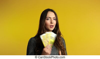 Carefree young woman counting euro banknotes and show stack...