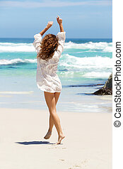 Carefree young woman in summer dress walking on beach