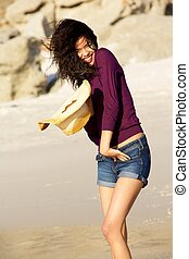 Carefree young woman walking on the beach