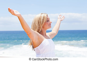 carefree young woman with arms open on beach