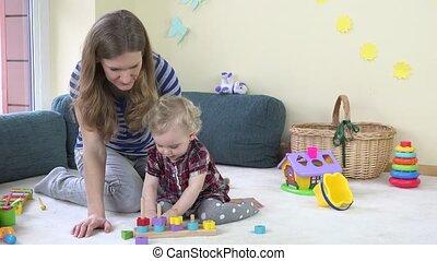 careful babysitter woman teach toddler girl pull wooden...