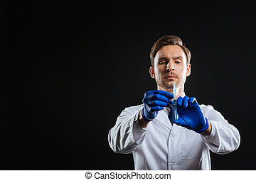 Careful calm doctor holding and dosing a syringe.