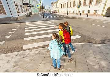 International children safely walking on street ready to cross the road and holding hands in the city during summer