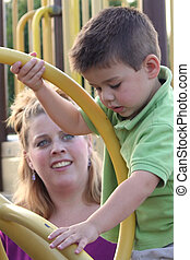 Young boy carefully climbing on playground equipment as his mother watches.