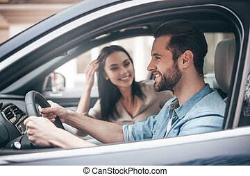 Careful driving. Beautiful young couple sitting on the front passenger seats and smiling while handsome man driving a car