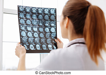 Careful excellent doctor having a better look at brain scans...