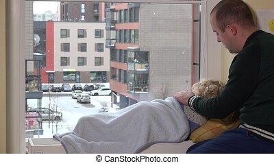 Careful father caress his kid lying on radiator near window....