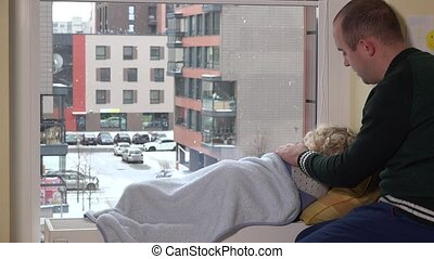 Careful father caress his kid lying on radiator near window. Snow falling