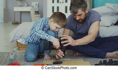Careful father is teaching his son to work with electric...