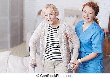 Careful female doctor helping her elderly patient to walk