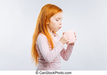 Careful kid blowing at cup - So hot. Attentive girl standing...