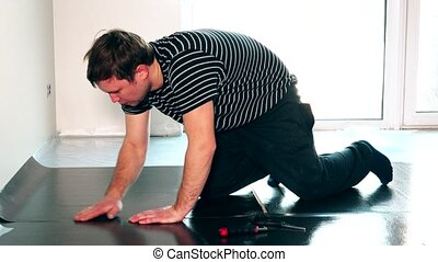 careful male worker man laying underlay for the laminate flooring installation