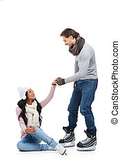 Careful man helping his girlfriend to stand up after falling on skating ring. Isolated on white
