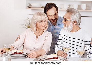 Careful mature son enjoying family dinner with parents at home