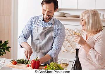 Careful mature son helping aged mother in the kitchen