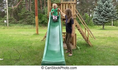Careful mother help her toddler daughter to slide down in playground.