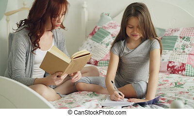 Careful mother helping her little cute daughter with homework for elementary school. Loving mom reading a book and girl writing notes in copybook while sitting together on bed at home