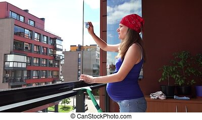 careful pregnant woman wipe window dust in flat house...
