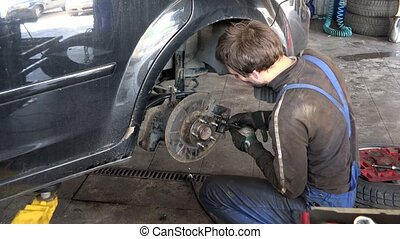 careful worker guy repairing car brake system in garage.