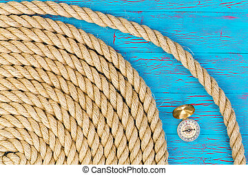 Carefully wound rope with compass over blue