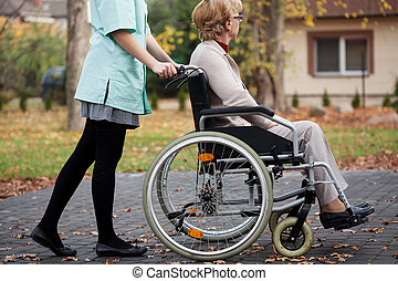 Caregiver on a relaxing walk with elder woman on wheelchair