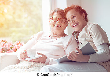 Caregiver and senior woman laughing - Young caregiver and...
